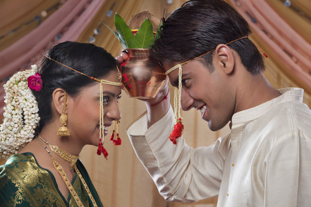 Bride and groom looking at each other while performing rituals