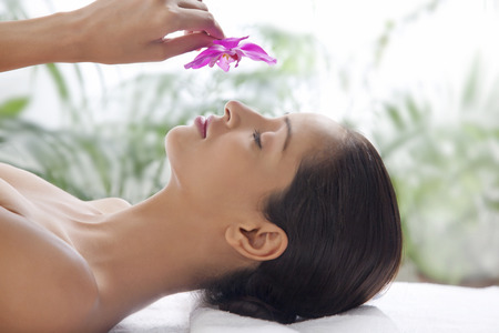 Young woman on massage table smelling flower LANG_EVOIMAGES