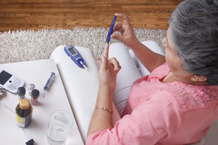 Diabetic old woman testing blood sugar