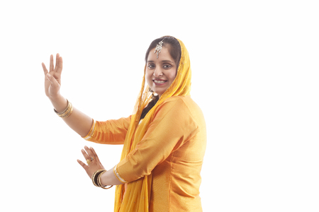 Portrait of Sikh woman doing bhangra dance LANG_EVOIMAGES