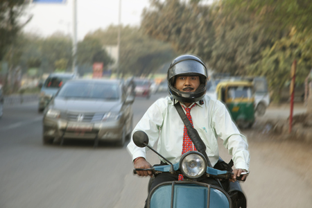 Salesman riding scooter in traffic, smiling