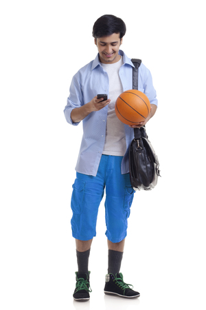 Portrait of young man with briefcase and basket ball using mobile phone