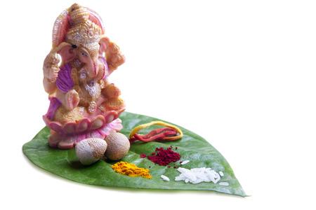 Lord Ganesha idol placed on Betel Leaf with Rice,Areca nut,Red thread,Kumkum and Turmeric