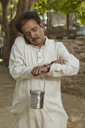 Man talking on cell phone and holding milk canister looking at watch LANG_EVOIMAGES