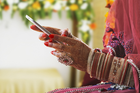 Close-up of a Brides hand using mobile phone