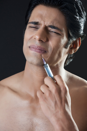 Portrait of man giving himself botox injection LANG_EVOIMAGES