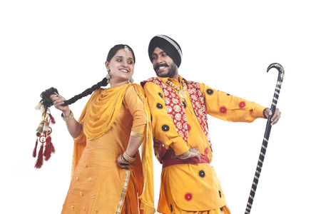 Sikh couple standing back to back