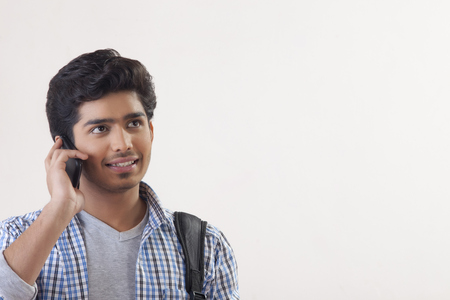 Smiling male college student using mobile phone