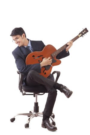 Smiling young man in formal clothes playing guitar, sitting on revolving chair against white background LANG_EVOIMAGES