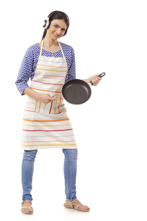 Young Indian woman holding kitchen utensil against white background
