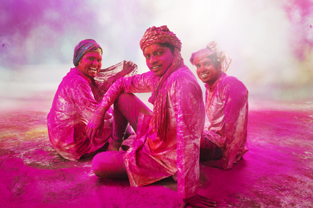 Young Indian Men sitting on floor, covered in colored powder during holi color festival