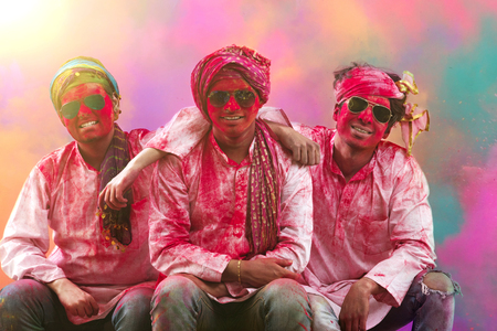 Young Indian Men sitting on bench, covered in colored powder during holi color festival LANG_EVOIMAGES