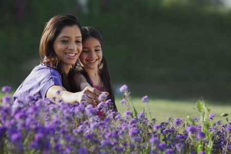 Mother and daughter plucking flowers LANG_EVOIMAGES