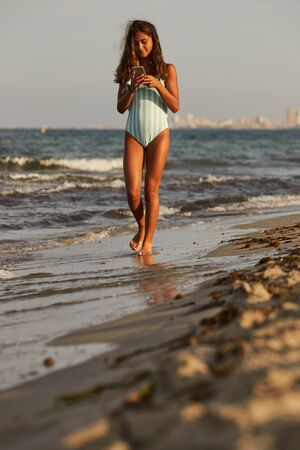 Young girl walking on the beach with mobile phone Zdjęcie Seryjne
