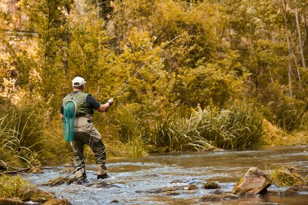 Man fishing for trout and salmon in a river