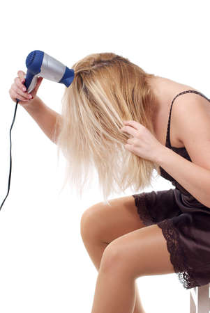 The young woman stacks hair by means of a hair drier