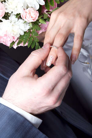 The groom puts on to the bride a gold ring photo