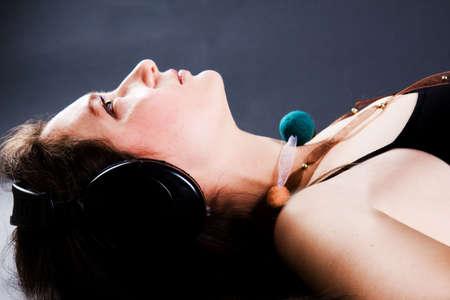 The beautiful woman listens to music through headphones photo