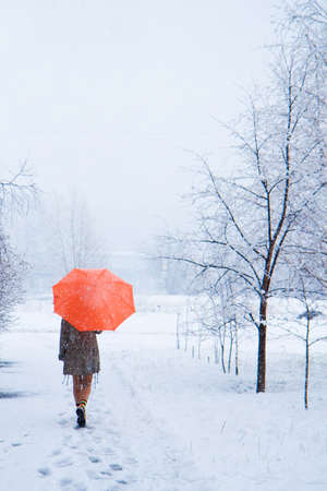 The passerby with an orange umbrella in snow park photo
