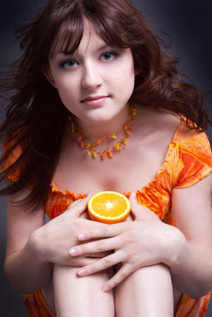 The positive smiling girl with an orange in hands photo