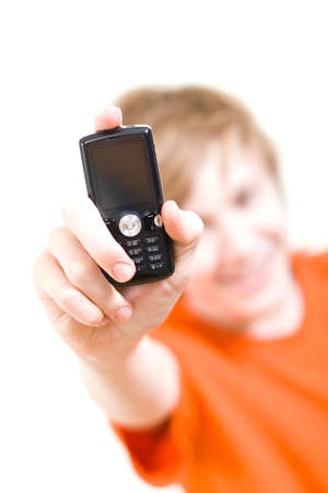 The teenager in an orange T-shirt holds a cellular telephone Stock Photo - 4207850