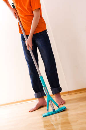 The teenager in an orange T-shirt washes a floor