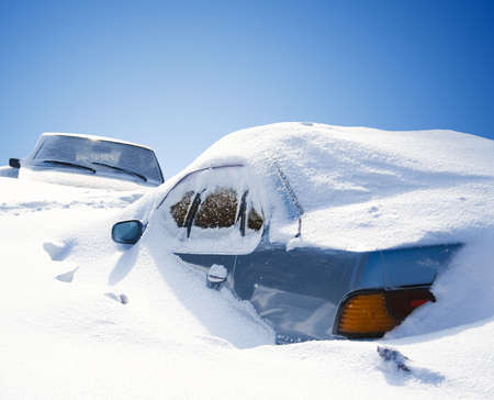 cars covered with snow in the winter blizzard