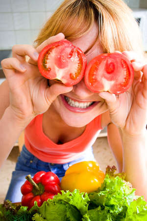The laughing loudly girl holds a tomato Stock Photo