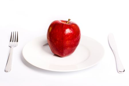 Red apple on white plate with knife and fork, with soft shadow Stock Photo - 6590235