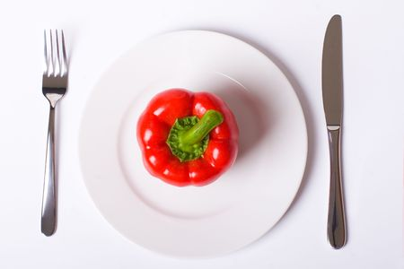 Red paprika on white plate with knife and fork, with soft shadow photo