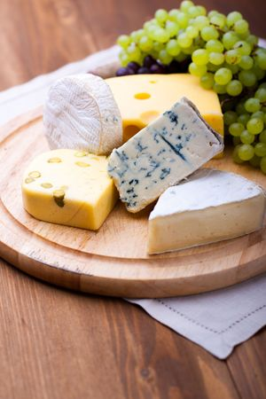 big group of cheeses with white grapes
