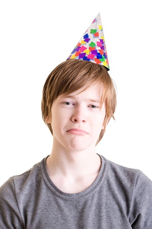 Tired sad teenager in a festive hat  Portrait on a white background photo