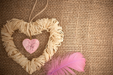 Valentines Day. Handmade Hearts made of bark and straw with feather . Love concept. photo