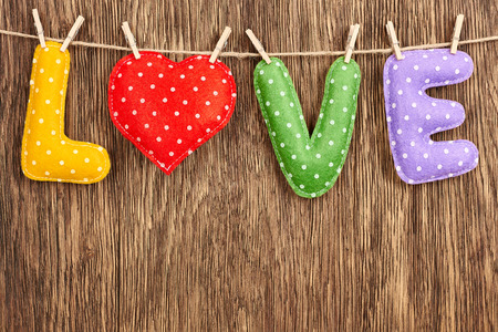 Valentines Day. Word Love dots, Heart Handmade, hanging on rope. Vintage style. Love concept on wooden background photo