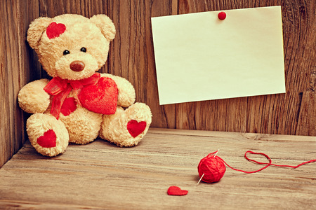 teddy bear baby: Valentines Day. Teddy Bear Loving with red hearts, note and  tangle of sewing thread. Vintage. Retro Styled on wooden background Stock Photo