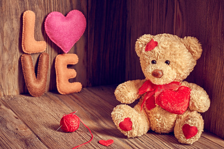 teddy bear love: Valentines Day. Teddy Bear Loving with red hearts, Handmade word Love. Vintage. Retro Styled on wooden background