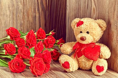 vintage teddy bears: San Valentino. Teddy Bear Amare con bouquet di rose rosse, Vintage. Stile retr�. Concetto di amore su sfondo di legno