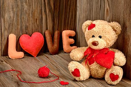 バレンタインの日。赤いハート、手作り単語愛のテディベア愛する。ヴィンテージ。木製の背景にレトロなスタイル