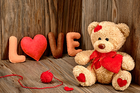 Valentines Day. Teddy Bear Milující s červeným srdcem, ruční slova láska. Vintage. Retro stylu na dřevěné pozadí