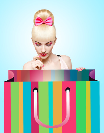 Glamorous girl looking into huge shopping bag waiting for presents, Pin up hairstyle. Concept for discounts and sales photo