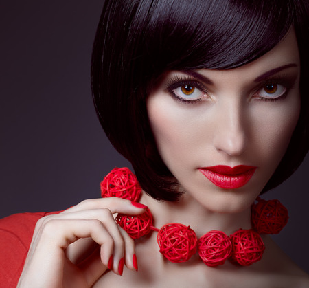 silky hair: Beautiful portrait brunette girl with smooth, silky hair and stylish necklace. Fashionable bob hairstyle, red nails. Beautiful red sexy lips. Stock Photo