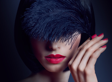 Beautiful portrait brunette girl with silky hair and black feather. Fashionable bob hairstyle, red nails and lipstick in the darkness, mystery photo