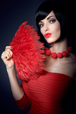 silky hair: Beautiful portrait brunette girl with smooth, silky hair and stylish red necklace, red feather fan. Fashionable bob hairstyle, red nails. Beautiful red sexy lips. Stock Photo