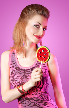 Beautiful Glamorous redhead girl portrait with fun hairstyle and big lollipop smiling  on pink background photo