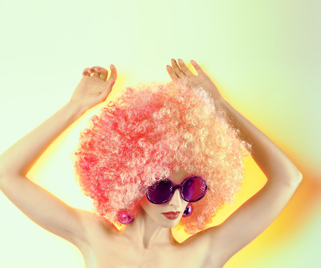 young teen girl nude: Portrait of Fashion nude girl in fashionable sunglasses with trendy afro hairstyle. Pose hands up. Perfect glowing skin. Sexy provocative look. Beauty curly woman face closeup