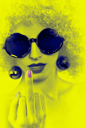 Portrait of Fashion nude hipster girl showing middle finger. Fashionable sunglasses and trendy afro hairstyle. Sexy provocative look. Party curly woman face closeup. Creative vintage style
