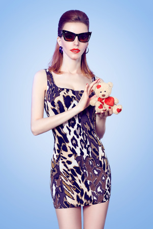sexy teen girl: Portrait of Fashion redhead woman in fashionable sunglasses with red lips. Sexy lady holds loving teddy bear with red heart. Perfect glowing skin. Beautiful girl vintage styled.