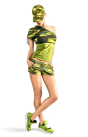 camouflage woman: Sexy blond woman wearing military camouflage style clothing and cap. Seductive Army girl looking down with hands in pockets. Red lips and pigtail hairstyle.  Isolated on white background, copyspace