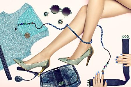 Dames sexy slanke benen in luxe schoenen met Set van stijlvolle glanzend kleding en accessoires. Glamoureuze look met trendy T-shirt en koppeling. Modieuze kettingen en een zonnebril. Elegante stijl voor de partij.