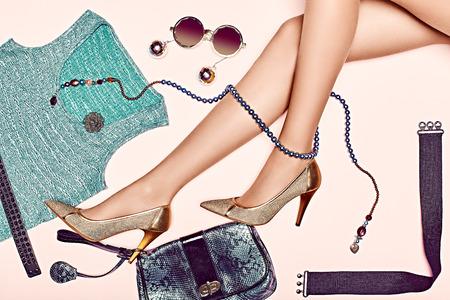 Kvinna sexig smala ben i lyx skor med uppsättning av snygga blanka kläder och accessoarer. Glamorös look med trendiga T-shirt och koppling. Fashionabla halsband och solglasögon. Elegant stil för fest. Stockfoto